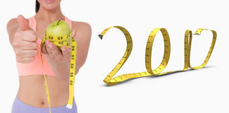 image 3D composée de femme mince tenant la pomme avec la bande de mesure Photographie stock