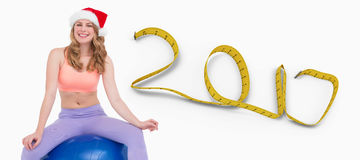 image 3D composée de la femme blonde de sourire s'asseyant sur la boule d'exercice Photo stock