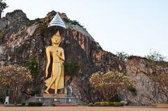 Image d'or de Bouddha sur la falaise Images stock
