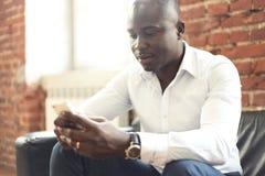 Image d'homme d'affaires professionnel d'afro-américain dans le vêtement formel d'affaires sur son smartphone mobile de cellules Photo stock