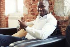 Image d'homme d'affaires professionnel d'afro-américain dans le vêtement formel d'affaires sur son smartphone mobile de cellules Image stock