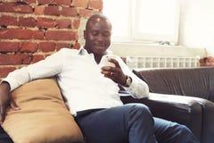 Image d'homme d'affaires professionnel d'afro-américain dans le vêtement formel d'affaires sur son smartphone mobile de cellules Photos stock