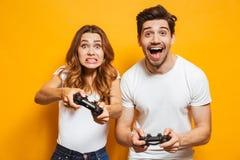 Image d'homme joyeux et de femme contrariée jouant ensemble la vidéo photos stock