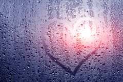 Image d'un coeur et un point d'interrogation sur une fenêtre misted humide Emo Photographie stock libre de droits