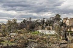 Image d'un courant entre une terre aride avec les arbres secs à côté des ruines d'un vieux pont avec un moulin à eau photos stock
