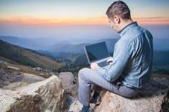 Image d'un homme d'affaires sur le dessus de la montagne, utilisant un ordinateur portable Images stock