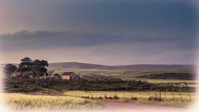 Image d'un paysage naturel dans des couleurs douces avec une maison, des arbres, un ciel foncé, les champs verts avec une haie et Photos stock