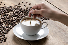 Image d'une tasse de café remué par une main humaine blanche, sur un dessus de table en bois images stock