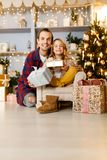 Image of dad girl with gift background of Christmas decorations in studio. Image of dad girl with gift in hands of sitting in chair on background of Christmas Stock Photography