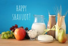 Image of dairy products and fruits over wooden table. Symbols of jewish holiday - Shavuot. Image of dairy products and fruits over wooden table. Symbols of stock photos