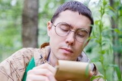 Image of dark-haired biologist in glasses. Writes in notebook at forest among plants and trees in summer afternoon Royalty Free Stock Photo