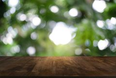 Image of dark wooden table in front of abstract blurred background of outdoor garden lights. can be used for display or montage y stock image