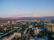 Image de bourdon au-dessus de ville au coucher du soleil avec des montagnes Image stock