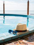 Image de chapeau et de lunettes de soleil par la piscine Photo libre de droits