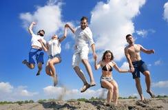 Image de cinq personnes énergiques sautant à la plage Image libre de droits