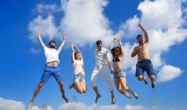 Image de cinq personnes énergiques sautant à la plage Photographie stock libre de droits