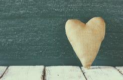 Image de coeur de tissu de vintage sur la table en bois devant le tableau noir Image stock
