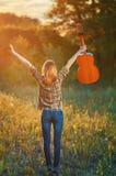 Image de derrière d'une jeune femme heureuse sur la chemise et les blues-jean de plaid Photos libres de droits
