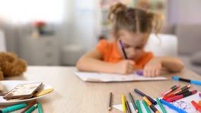 Image de dessin de fille, crayons d'astuce de feutre et casse-croûte doux sur la table, passe-temps photos stock