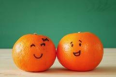 Image de deux clémentines avec les visages souriants tirés Image libre de droits