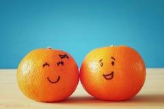 Image de deux clémentines avec les visages souriants tirés Photos stock