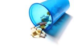 Image de différentes pilules se renversant hors d'un verre en plastique Photo libre de droits
