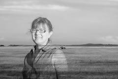 Image de double exposition d'une femme se tenant dans un domaine avec un tracteur sur la terre Photo libre de droits