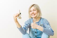 Image de femme avec des clés d'appartement contre le mur vide Images stock