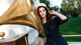 Image de femme dans la robe et le chapeau noirs à côté du phonographe image libre de droits