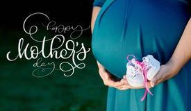 Image de femme enceinte touchant son ventre avec le jour heureux de mains et de mères des textes Aspiration de main de lettrage d Photographie stock libre de droits