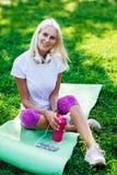 Image de femme sportive dans des écouteurs, avec la bouteille Images stock
