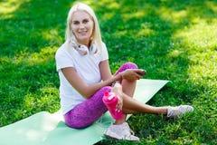 Image de fille de sports dans des écouteurs, avec la bouteille Photographie stock