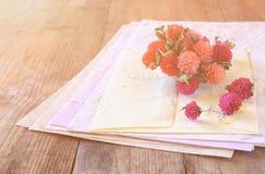 Image de foyer sélectif des fleurs sèches et du papier de lettres fabriqué à la main de vintage sur la table en bois rétro image  Image stock