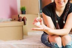 Image de jeune brune avec des clés d'appartement contre le mur vide Photographie stock libre de droits