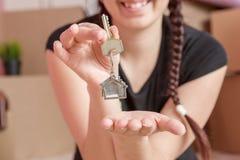 Image de jeune brune avec des clés d'appartement contre le mur vide Photos stock