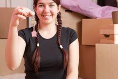 Image de jeune brune avec des clés d'appartement contre le mur vide Photo stock
