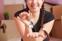 Image de jeune brune avec des clés d'appartement contre le mur vide Image stock