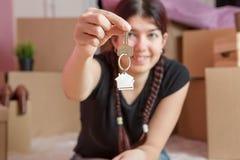 Image de jeune brune avec des clés d'appartement contre le mur vide Images stock