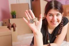 Image de jeune brune avec des clés d'appartement contre le mur vide Image libre de droits