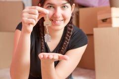 Image de jeune brune avec des clés d'appartement contre le mur vide Photo libre de droits