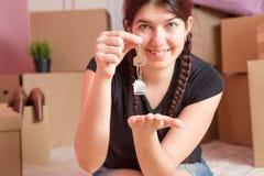Image de jeune brune avec des clés d'appartement contre le mur vide Photographie stock