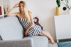 Image de jeune femme se reposant sur le sofa gris Images libres de droits