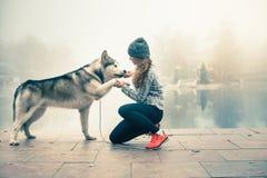 Image de jeune fille avec son chien, malamute d'Alaska, extérieur Photo stock