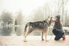 Image de jeune fille fonctionnant avec son chien, malamute d'Alaska Photos stock