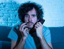 Image de jeune homme regardant la s?ance d?go?t?e sur le sofa observant le film violent ? la TV la nuit image libre de droits