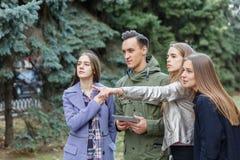 Image de jeunes amis dehors avec un ordinateur dans des mains d'un jeune homme Image stock