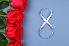 Image de jour de femmes avec une rose rose attachée avec un ruban dans la forme du numéro 8 Concept 8 mars Photographie stock libre de droits