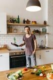 Image de l'homme avec la poêle dans des mains dans la cuisine Image stock