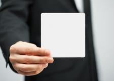 Homme dans le costume tenant la carte vierge Images stock