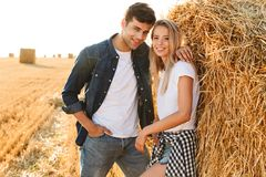 Image de l'homme et de la femme de sourire de couples marchant sur le champ d'or, a photos stock